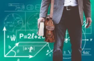 professor with book math algorithms on chalkboard behind