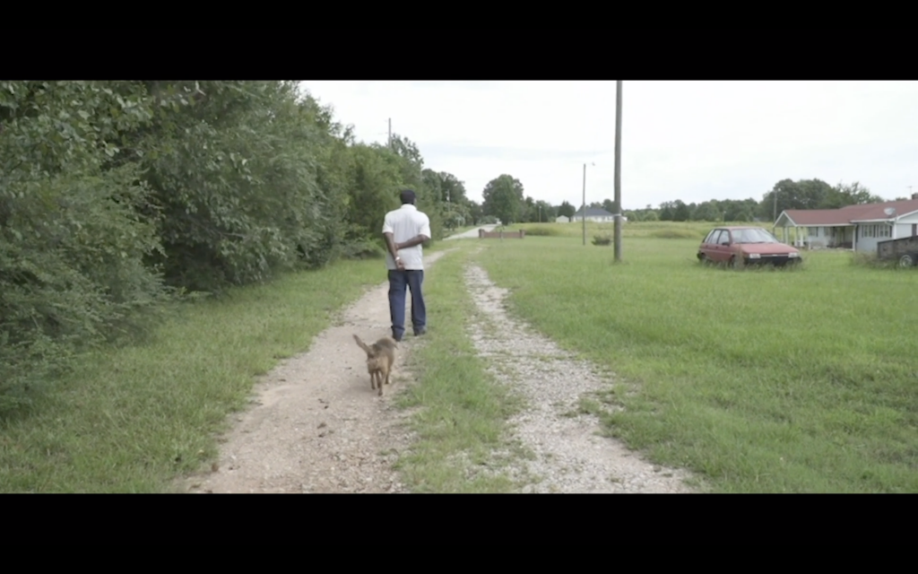 screenshot from film- AQ Jackson walking with dog